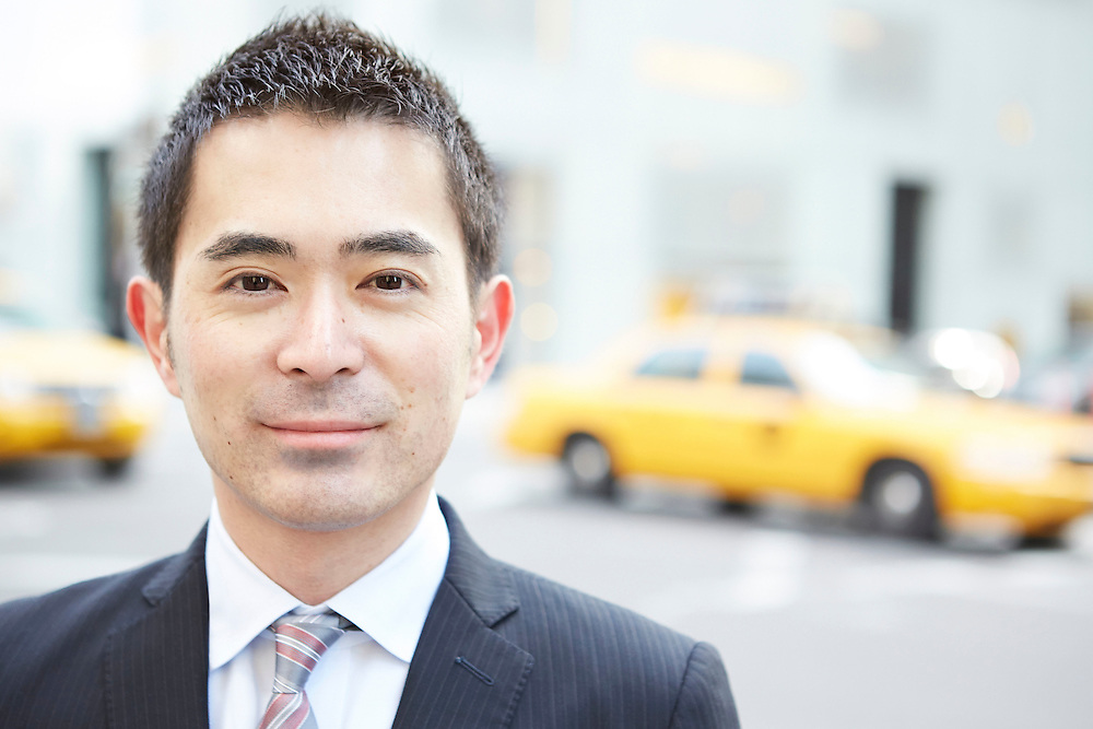 Asian businessman in Midtown East New York City with yellow cabs in background