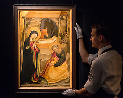 """© Licensed to London News Pictures. 02/12/2016. London, UK. A technician shows """"Nativity"""" by Bicci di Lorenzo, , a 15th century, Italian gold-ground 'gabella' panel, (est. GBP 300-500k), at a preview of Sotheby's upcoming Old Masters Evening Sale in New Bond Street. Photo credit : Stephen Chung/LNP"""