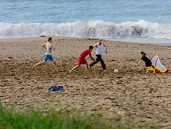 Girl and boys playing soccer with  father on the beach