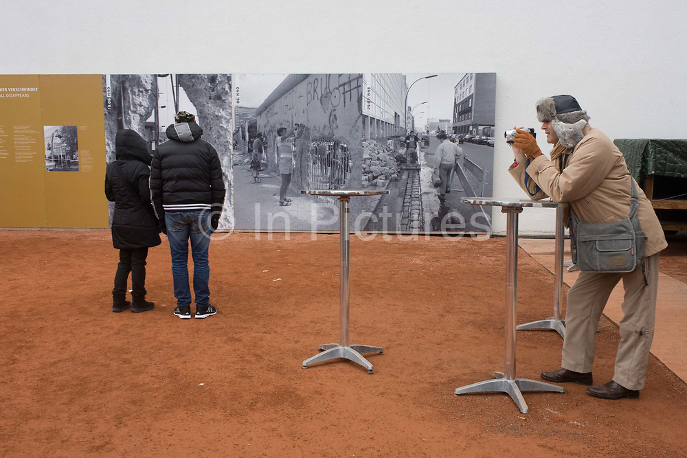 """Visitors learning about the Berlin Wall read outdoor exhibition panels near the former Checkpoint Charlie, the former border between Communist East and West Berlin during the Cold War. The Berlin Wall was a barrier constructed by the German Democratic Republic (GDR, East Germany) starting on 13 August 1961, that completely cut off (by land) West Berlin from surrounding East Germany and from East Berlin. The Eastern Bloc claimed that the wall was erected to protect its population from fascist elements conspiring to prevent the """"will of the people"""" in building a socialist state in East Germany. In practice, the Wall served to prevent the massive emigration and defection that marked Germany and the communist Eastern Bloc during the post-World War II period."""