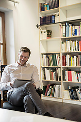 Mid adult businessman using digital tablet in an office and smiling, Bavaria, Germany