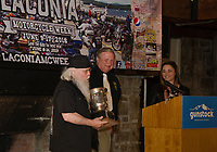 """K. Peddlar Bridges receiving a trophy for his """"historian"""" work from Charlie St. Clair and Jennifer Anderson during the kickoff event at Gunstock on Thursday.  (Karen Bobotas/for the Laconia Daily Sun)"""