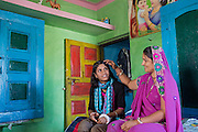 Ritu Gaur, 13, is sitting in her family home in Chittawaliya village, rural Sehore, while her mother Mohini, 37, is caressing her hair. Ritu lives in the Jamoniya Tank Girls Hostel by her school, near Sehore, Madhya Pradesh, India, where the Unicef India Sport For Development Project has started in 2012. Covering 313 state-run girls' hostels and 207 mixed hostels in Madhya Pradesh, the project ensures that children from Scheduled Tribes (ST) and others amongst the poorest people in India, can easily access education and be introduced to sports. Field workers from Unicef also oversee their nutrition and monitor the overall conditions of each pupil.