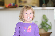 A little girl playfully laughs while at home in Atlanta, GA