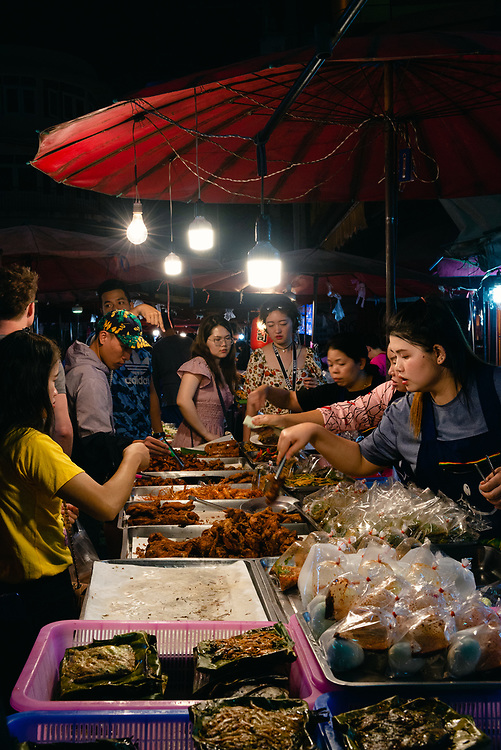 Street stalls serving snack food at a local night market in Chiang Mai,