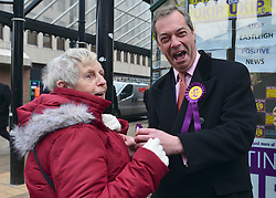© Licensed to London News Pictures. 27/02/2013. Eastleigh, UK Nigel garage pins a rosette to a lady in the street. UKIP leader Nigel Farage and UKIP candidate Diane James campaign in Eastleigh town centre today 27th February 2013. Voting in the Eastleigh by-election takes place tomorrow (28/02/13). Photo credit : Stephen Simpson/LNP
