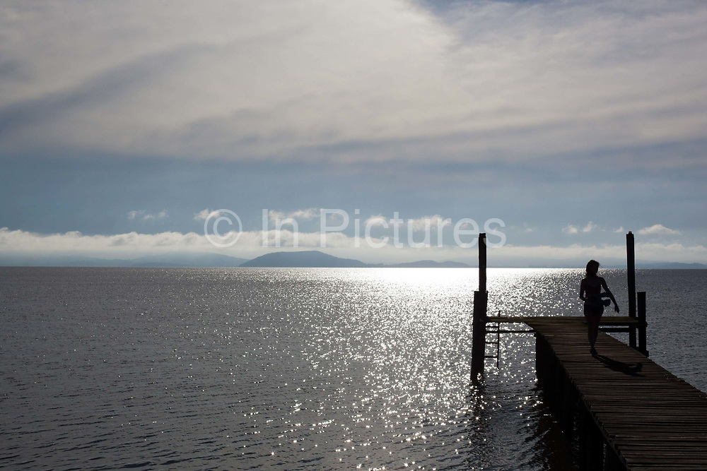 Young female figure silhouette, sitting on the end of a jetty on the banks of a lake at dawn, showing vanishing point. Working Gaucho Fazenda in Rio Grande do Sul, Brazil.