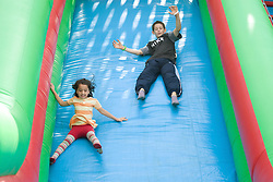 Children enjoying the big inflatable slide at a Parklife summer activities event,