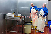 Ernest 'Ginger' Peacham (r) and Simon Brennan washing down after gutting and chopping eels on the last day at the historic Barneys Seafood in Aldgate before a move to Billingsgate Market. The famous wholesale jellied eel and shellfish business started in 1969 supplying Pie and Mash shops and shellfish stalls in East London. Jellied eels are a traditional London dish. London, United Kingdom.