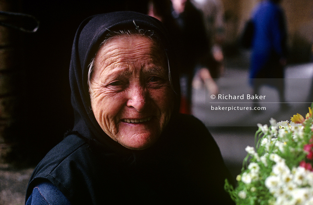 An elderly Hungarian woman pauses to smile at the viewer during a busy morning in Budapest's Central Market Hall (Hungarian: Nagycsarnok), on F?vám Tér in the 9th district. The market is the largest indoor market in the Hungarian capital and is where this lady and many other market traders converge on every weekday morning to sell their own produce. This woman has a lined face suggesting she has had a hard life under a Communist regime. She still wears a traditional Hungarian covered head favoured by older people in rural communities but is now dying out as headwear for a younger generation.