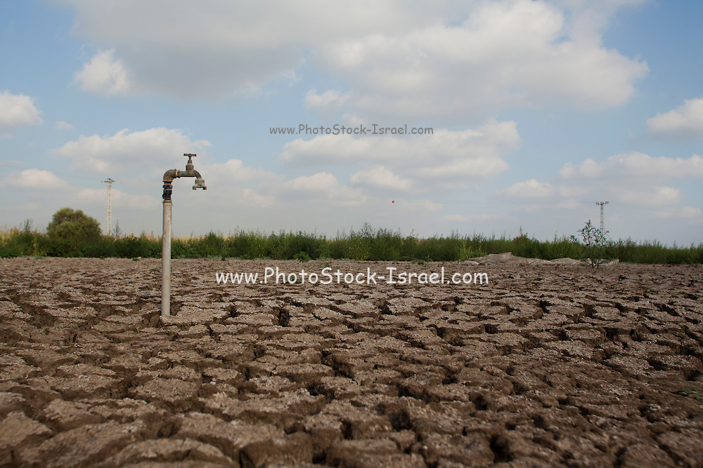environmental concept, Water shortage and drought Dry cracked mud with a water faucet