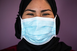 © Licensed to London News Pictures . 21/05/2020 . Manchester , UK . Senior Diagnostic Radiographer AMAL SALAH (28 from Longsight) dons a basic face mask after being fit-tested for an FFP3 type . Due to the Covid-19 outbreak , fit testing has been scaled up by the hospital , in an effort to provide more effective protection for as many staff as possible . Specialist cancer centre , The Christie Hospital , is adapting in order to ensure the safety of patients and staff . They are reporting a drop in referrals during the UK's Coronavirus lockdown and there is concern that cancers are going undiagnosed and untreated . Photo credit : Joel Goodman/LNP