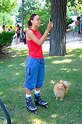 Asian teen woman photographing festival ceremony with cell phone. Dragon Festival Lake Phalen Park St Paul Minnesota USA