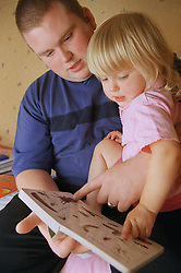 Father reading picture book with daughter,