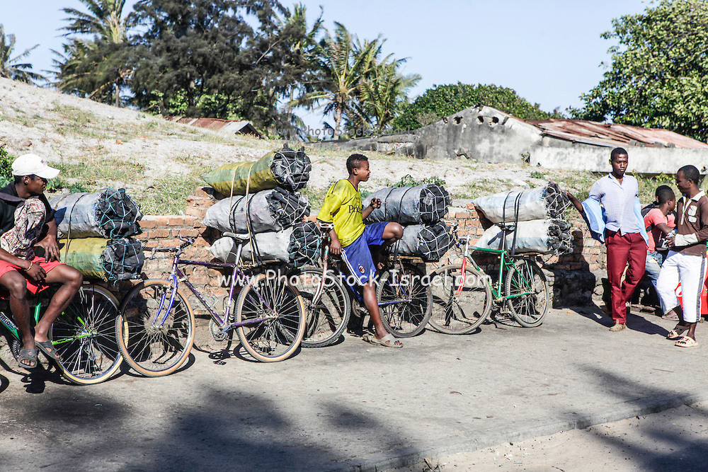 Madagascar Charcoal industry. Sacks of charcoal being transported on bicycles