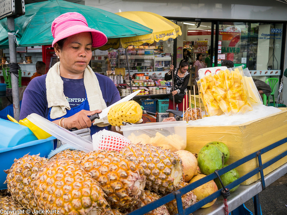 09 OCTOBER 2012 - BANGKOK, THAILAND:  A pineapple vendor cuts up a pineapple in front of the Bangkok Flower Market. The Bangkok Flower Market (Pak Klong Talad) is the biggest wholesale and retail fresh flower market in Bangkok. It is also one of the largest fresh fruit and produce markets in the city. The market is located in the old part of the city, south of Wat Po (Temple of the Reclining Buddha) and the Grand Palace.    PHOTO BY JACK KURTZ