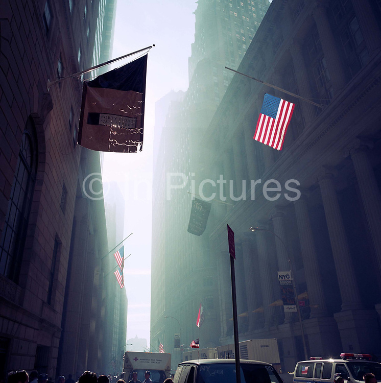The Monday morning following the attacks on the World Trade Center on Septmber 11th we see a dust-filled haze on Wall Street to where city financiers returned to their office desks to find their city skyline missing the Twin Towers and Manhattan in a state of perpetual shock and still under a mist of smoke from the debris at Ground Zero. To celebrate the near-return to financial normality, New Yorkers' spirit was proved intact by the hanging of US flags from buildings. An American flag hangs and a banner for 48 Wall Street, known as the Bank of New York Building (built in 1928 on land used by the bank since 1797), on the corner of Wall Street and William Street in New York City's Financial District.