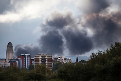 © Licensed to London News Pictures. 07/10/2016. Leeds UK. Picture shows smoke bellowing across Leeds city skyline as the second large industrial fire in Leeds today takes hold. The fire is at the former Polestar Petty printing warehouse on Whitehall Road. Photo credit: Andrew McCaren/LNP
