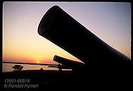 Barrels of two Civil War cannons loom against purplish sky at sunset; Fort McHenry, Baltimore. Maryland
