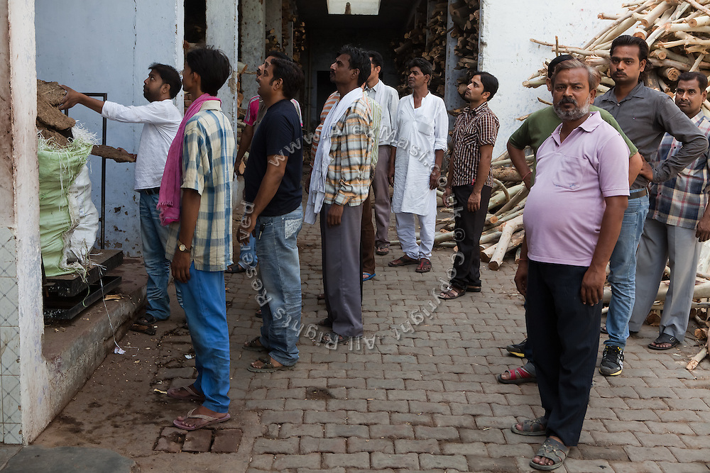 Relatives of a deceased person are purchasing wood at the traditional 'burning ghat' in Agra.