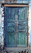 A weathered green door in Cuzco (Cusco or Qosqo), Peru, South America. Cuzco was the site of the historic capital of the Inca Empire from the 1200s to 1532 and was honored on the World Heritage List in 1983 by UNESCO. Francisco Pizarro officially founded Spanish Cuzco in 1534. Cuzco is the longest continuously occupied city in the Americas and is built upon the foundations of the Incas at 3400 meters or 11,200 feet elevation.