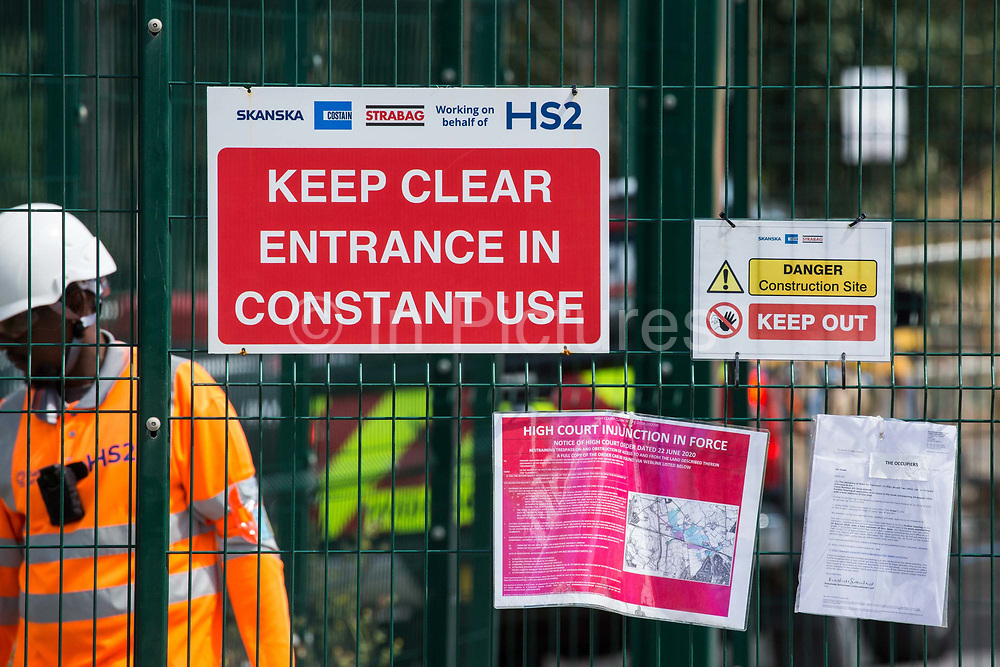 Warning notices are displayed outside a gate to a construction site for the HS2 high-speed rail link on 29th July 2020 in Harefield, United Kingdom. Environmental activists based in the vicinity have been trying to disrupt HS2's activities in the Colne Valley including the felling of many thousands of trees and drilling into the chalk aquifer.
