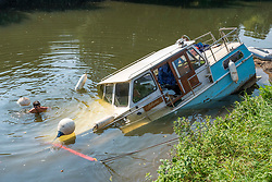 "© Licensed to London News Pictures; 16/09/2020; Bath, UK. The canal boat ""Pollyanna"" is seen partly submerged on the river Avon in Bath as Harry a friend of the owner works to attach a recovery line. Canal boats were evacuated and some boats sunk on the river Avon at Twerton after the sluice gates failed yesterday evening (15 September) and the water level dropped dramatically. The Fire Service assisted. The Canal and River Trust have issued a statement saying a drop in water level on the River Avon was caused by a failure of the Environment Agency's sluice gates and that the sudden and dramatic drop in levels meant that it was impossible to give warning to the boaters. The Canal and River Trust say they understand the difficulties faced by the EA in repairing the sluice and this is the second time this has happened, so they are looking to the EA to find a solution as a matter of urgency.  Photo credit: Simon Chapman/LNP."