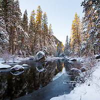The icy river contrasts the warm sun creeping in behind the trees.  Camping here can be a challenge in the winter. © John McBrayer