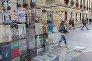A reflection of books in a bookshop window and pedestrians crossing the road with a pet dog, on 24th September 2019, in Krakow, Malopolska, Poland.