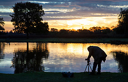 © Licensed to London News Pictures. 03/11/2018. London, UK. A photographer lines up a shot of Heron Pond at sunrise in Bushy Park, south west London. The remains of hurricane Oscar are expected affect parts of the UK overnight bringing high winds and rain. Photo credit: Peter Macdiarmid/LNP