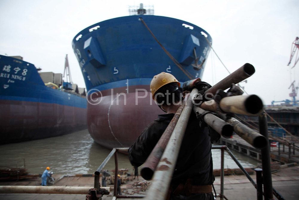 Workers travels through the China CSSC Holdings Ltd. Chengxi Shipyard in Jiangyin, China, on Sunday, Sept. 12, 2010. China CSSC Holdings Ltd., the nation's biggest shipyard, sees orders surge as China's voracious appetite for commodities demands more fleets of large vessels.