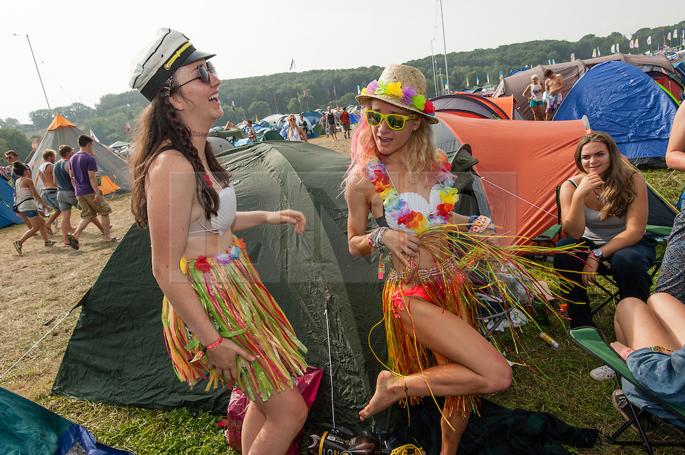 © Licensed to London News Pictures. 06/09/2014. Isle of Wight, UK. A group of female festival goers at Bestival 2014 Day 3 Saturday get their outfits ready for the fancy dress day ahead - they are dressed in hula skirts, shell bikini tops, sailors hats and glittery makeup.   Today is the festival's Fancy Dress Day - this year the theme is Desert Island Disco.  Festival goers spend the morning readying their costumes before the judging of the competition at 2pm.  This weekend's headliners include Chic featuring Nile Rodgers, Foals and Outcast.   Bestival is a four-day music festival held at the Robin Hill country park on the Isle of Wight, England. It has been held annually in late summer since 2004.    Photo credit : Richard Isaac/LNP