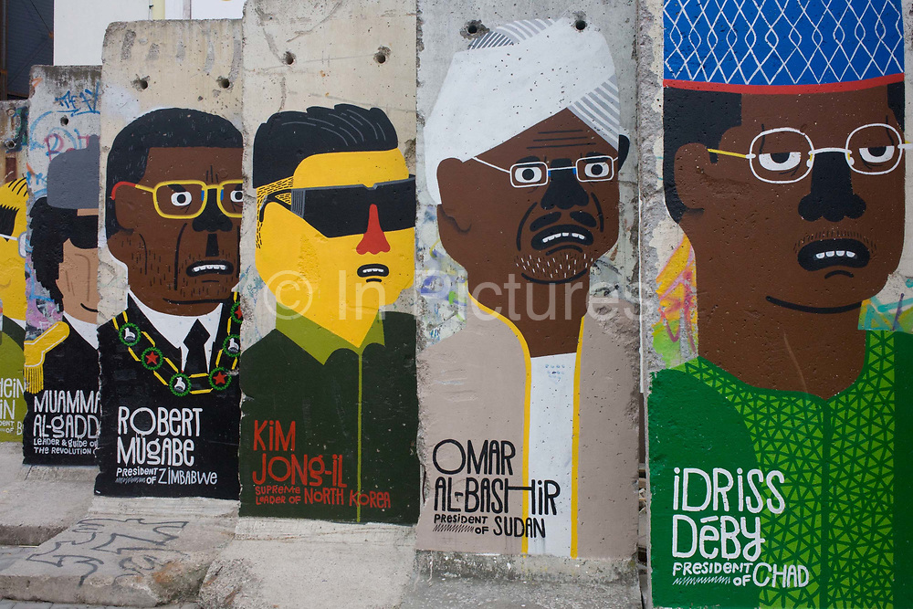 """World dictators adorn old sections of the old Berlin Wall <br /> opposite the former Checkpoint Charlie, the former border between Communist East and West Berlin during the Cold War. The Berlin Wall was a barrier constructed by the German Democratic Republic (GDR, East Germany) starting on 13 August 1961, that completely cut off (by land) West Berlin from surrounding East Germany and from East Berlin. The Eastern Bloc claimed that the wall was erected to protect its population from fascist elements conspiring to prevent the """"will of the people"""" in building a socialist state in East Germany. In practice, the Wall served to prevent the massive emigration and defection that marked Germany and the communist Eastern Bloc during the post-World War II period."""