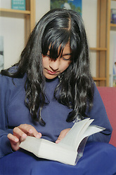 Secondary school pupil reading book in library,