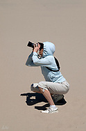 Julie with DSLR in sand dunes, Oregon Coast, squatting to get the shot.