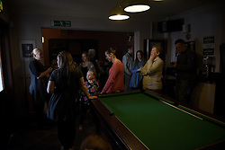 """© London News Pictures. """"Looking for Nigel"""". A body of work by photographer Mary Turner, studying UKIP leader Nigel Farage and his followers throughout the 2015 election campaign. PICTURE SHOWS - Local UKIP supporters in The Kings Head pub in Grimsby, Lincolnshire, await the arrival of Nigel Farage, to pull a pint of a local ale that has been named 'Farageale' in his honour, on April 8th 2015. However, the UKIP leader failed to arrive due to security concerns and instead went to a cafe around the corner for fish and chips with Joey Essex. . Photo credit: Mary Turner/LNP **PLEASE CALL TO ARRANGE FEE** **More images available on request**"""