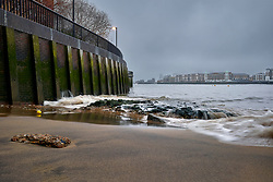 Small waves breaking over rocks onto a sandy beach beneath the River Thames Wall at Shadwell, London, on a foggy morning.