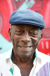 Elderly black man sitting in front of mural; Havana; Cuba,