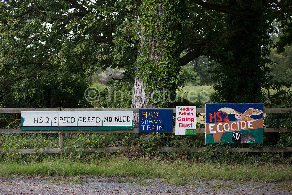 Anti-HS2 signs are pictured outside a farm close to HS2 tree felling sites at Leather Lane and Jones Hill Wood on 3rd August 2021 in Great Missenden, United Kingdom. A report by Professor Stephen Glaister for the Institute For Government think tank has suggested that the acceleration of a move to electric vehicles is eroding any small environmental benefits offered by the £106bn HS2 project due to the total carbon emissions required to build the railway.