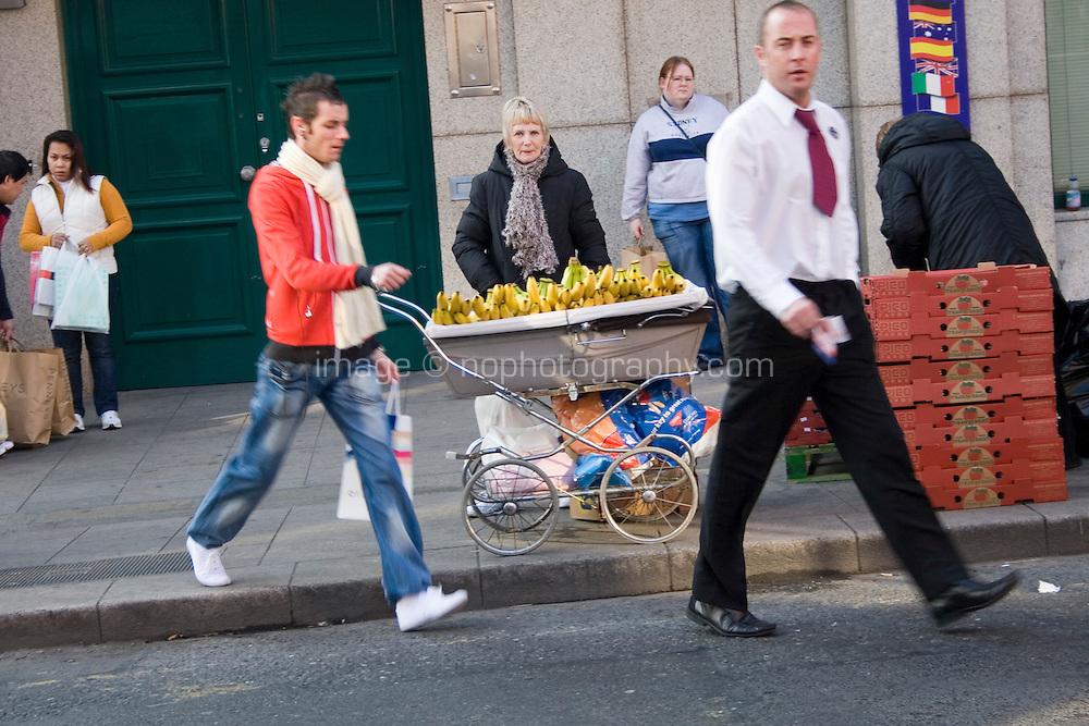 Woman selling banannas from a pram on Capel Street in Dublin Ireland