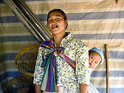 """A Laoseng minority woman carries her baby whilst smoking tobacco in her home in the remote and roadless village of Ban Phouxom, Phongsaly province, Lao PDR, Ban Phouxom is situated along the Nam Ou river (a tributary of the Mekong) and will be relocated and joined with three other Laoseng villages following the construction of the Nam Ou Cascade Hydropower Project Dam 5. The Nam Ou river connects small riverside villages and provides the rural population with food for fishing. It is a place where children play and families bathe, where men fish and women wash their clothes. But this river and others like it, that are the lifeline of rural communities and local economies are being blocked, diverted and decimated by dams. The Lao government hopes to transform the country into """"the battery of Southeast Asia"""" by exporting the power to Thailand and Vietnam."""