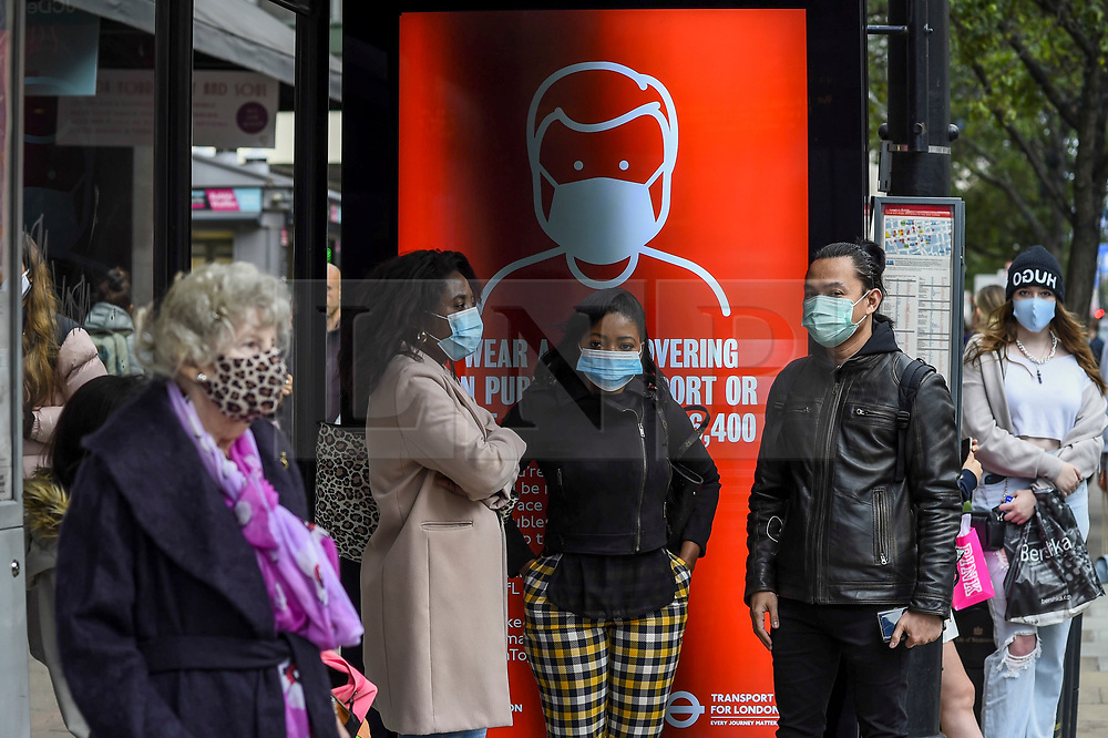 © Licensed to London News Pictures. 26/09/2020. LONDON, UK. Shoppers wearing facemasks at a bus stop on Oxford Street in the West End of the capital.  As the number of coronavirus cases continues to rise heralding a second wave of the pandemic, it is reported that London may soon face more comprehensive lockdown restrictions.  Photo credit: Stephen Chung/LNP