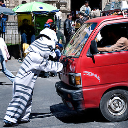 La Paz, Bolivia - March 27, 2008 - Luis Quispe Mamani, 19, pushes back a minivan driver who has overshot the crosswalk in front of the Catedral of La Paz on the Plaza Murillo...Photo by Susana Raab
