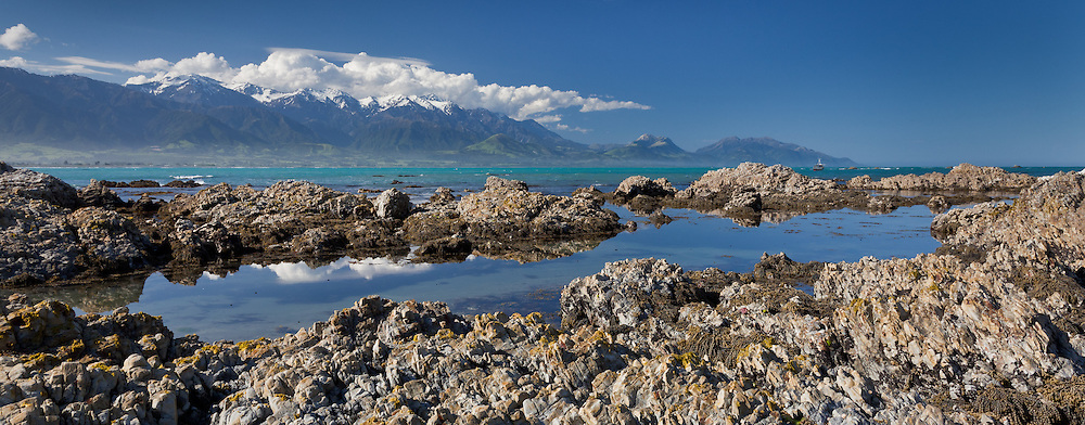 panoramic of limestone formations at low tide with the Kaikoura Seaward Range in the backdrop, New Zealand
