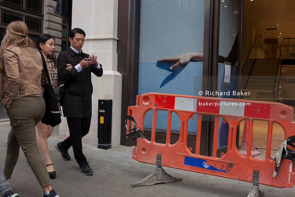 Passers-by walk past the disjointed hand outside a soon to open Jigsaw shop in central London.