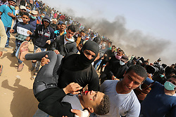 April 13, 2018 - Khan Younis, Gaza Strip, Palestinian Territory - A wounded Palestinian protester is evacuated during clashes with Israeli security forces in a tent city protest where Palestinians demand the right to return to their homeland, at the Israel-Gaza border, in Khan Younis in the southern Gaza Strip.   (Credit Image: © Ashraf Amra/APA Images via ZUMA Wire)