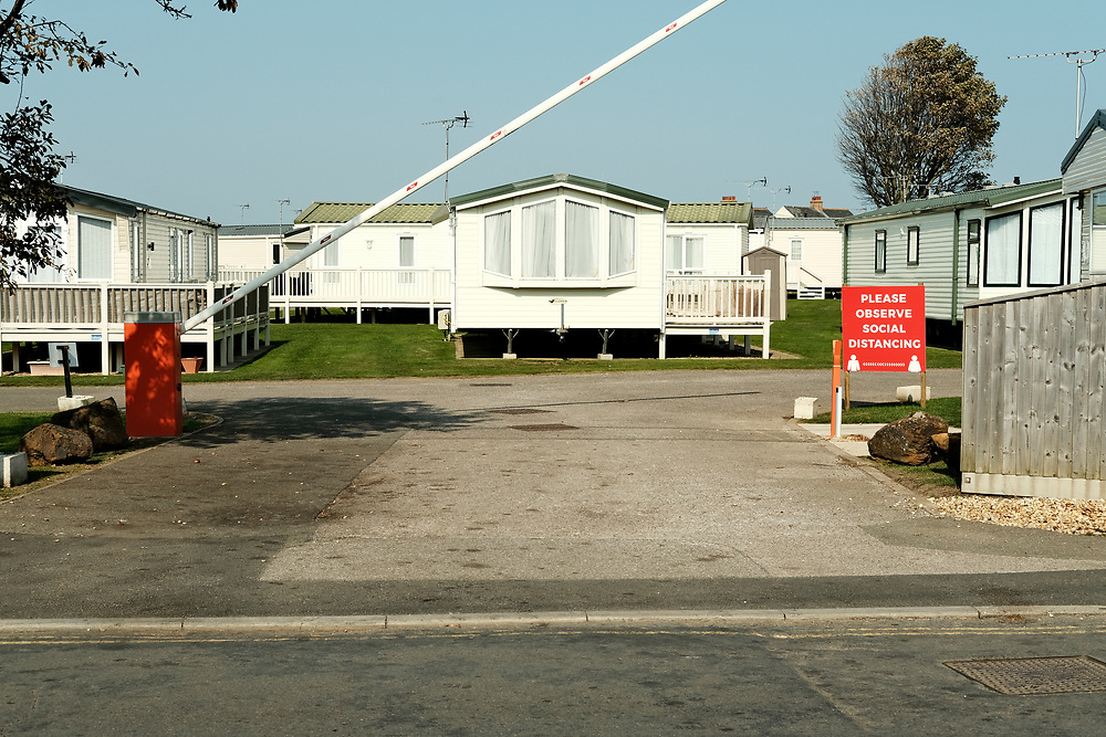 The barrier opens at the entrance of a static caravan site, signage asked you to observe social distancing. Taken on<br /> the last hot day of the Summer in Hunstanton Norfolk, the first summer in the UK during the COVID-19 pandemic.<br /> <br /> Photo by Jonathan J Fussell, COPYRIGHT 2020
