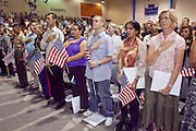 """04 JULY 2009 -- PHOENIX, AZ: Candidates for citizenship say the """"Pledge of Allegiance"""" before being sworn in as US citizens at a naturalization ceremony in Phoenix, AZ, July 4. U.S. Citizenship and Immigration Services and South Mountain Community College in Phoenix, AZ, hosted the 21st annual """"Fiesta of Independence"""" Saturday, July 4. More than 180 people from 58 countries took the US Oath of Citizenship and became naturalized US citizens. The ceremony was one of dozens of similar ceremonies held across the US this week. USCIS said more than 6,000 people were naturalized US citizens during the week.  Photo by Jack Kurtz / ZUMA Press"""