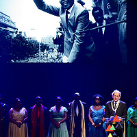 Nederland, Amsterdam , 15 december 2013.<br /> Herdenking Mandela.<br /> Prinses Beatrix is rond het middaguur aangekomen bij de Stadsschouwburg in Amsterdam. Zij woont daar het Nationaal Eerbetoon Samen door Mandela bij. Burgemeester Eberhard van der Laan van Amsterdam ontving de prinses op de rode loper voor de schouwburg.<br /> Voorafgaand aan het programma heeft Beatrix een ontmoeting met de initiatiefnemers van het eerbetoon, onder wie Conny Braam (oud-voorzitter Anti Apartheidsbeweging Nederland), Melle Daamen (directeur Stadsschouwburg) en zangeres en actrice Gerda Havertong. Namens het kabinet is minister Jet Bussemaker van Onderwijs, Cultuur en Wetenschap aanwezig.De aankomst van de prinses werd begeleid door een Afrikaanse drumband. Tientallen belangstellenden stonden langs de loper en voor de schouwburg mee te klappen, dansen en sommigen zongen 'Mandela! Mandela!'.<br /> Op de foto: Burgemeester Eberhard  van der laan samen met Cape Town Opera Choi tijdens speech in Stadsschouwburg.<br /> Foto:Jean-Pierre Jans