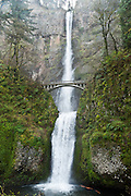 Multnomah Falls plunges 620 feet in two tiers in Columbia River Gorge National Scenic Area, adjacent to Interstate 84 and Historic Columbia River Highway, in Oregon, USA. A foot trail leads to Benson Footbridge, a 45-foot (14 m) long footbridge that allows visitors to cross 105 feet (32 m) above the lower cascade.